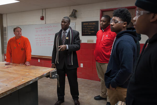 Jennings School District Superintendent Art McCoy, center, talks with students in a construction skills course at Jennings High School in January.