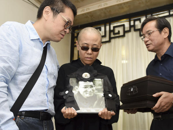 In a photo provided Saturday by the Shenyang Municipal Information Office, Liu Xia, center, the widow of Chinese dissident Liu Xiaobo, holds a portrait of him during his funeral. She stands with Liu Hui, her younger brother (left) and Liu Xiaoxuan, the younger brother of her late husband, who is holding his cremated remains.