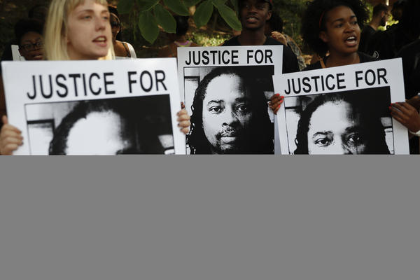 Protesters chant while holding signs showing Sam DuBose during a demonstration on the University of Cincinnati campus after the second mistrial of Ray Tensing last month in Cincinnati.