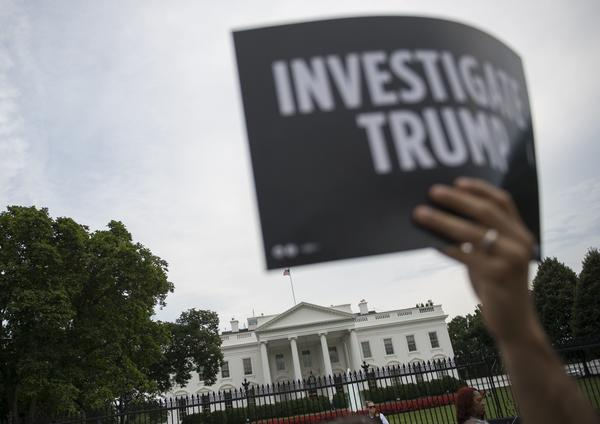 A protester holds up a sign during a July 11 rally calling for accountability regarding alleged collusion between the Trump campaign and the Russian government.