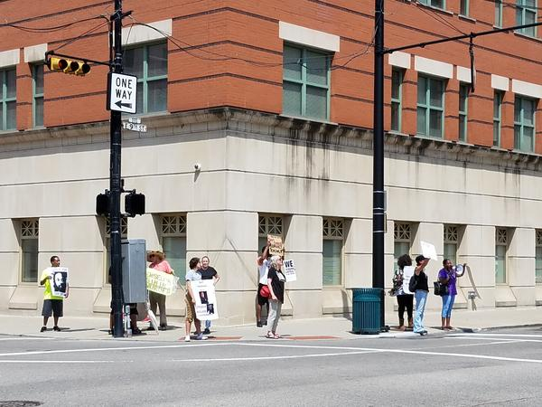 Protesters outside the Hamilton County Prosecutor's office chant and hold signs calling for Ray Tensing to be tried a third time for the death of Sam DuBose.
