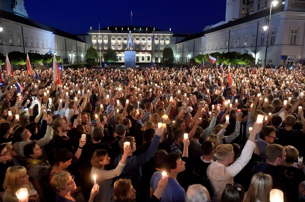 Protesters raise candles during a protest in front of the presidential palace in Warsaw on Tuesday, as they urge the Polish president to reject a bill giving the ruling party more control over the judiciary system. President Andrzej Duda made a surprise compromise bid over controversial court reforms, as protesters took to the streets.