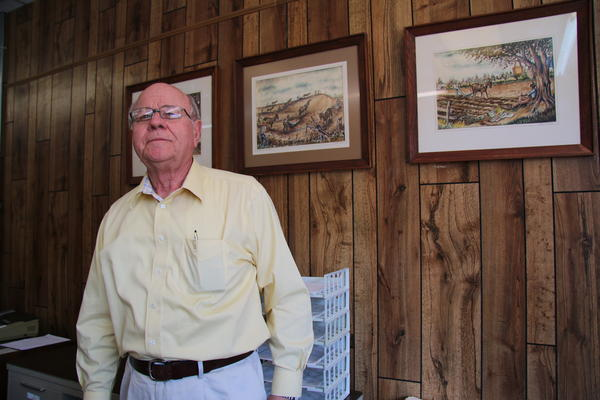 Earl Bullington,  advisor for Focus Bank, which rescued the struggling Pemiscot County hospital in 2013. The pictures on his wall depict the farmland in Pemiscot County, Missouri.