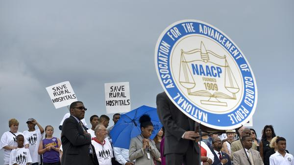 Attendees stand behind a sign with the NAACP's logo at a 2015 rally in Washington, D.C. The civil rights group is holding its annual convention in Baltimore this year.