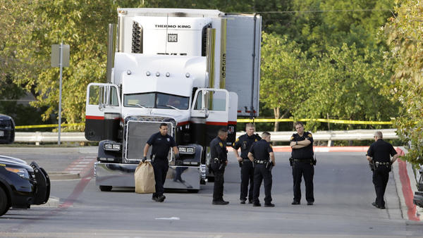 San Antonio police officers are seen in a parking lot where at least nine people were found dead in a tractor-trailer that contained at least 30 others outside a Walmart store.