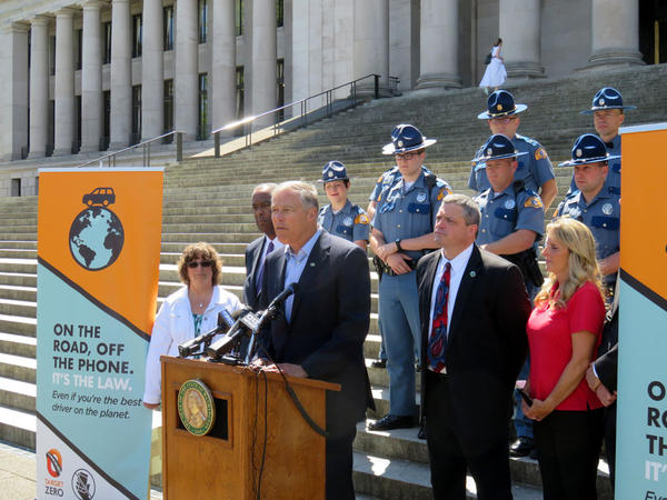 Washington Gov. Jay Inslee flanked by Tina Meyer, the mother of a distracted driving crash victim, at far left, on the state Capitol steps Monday.