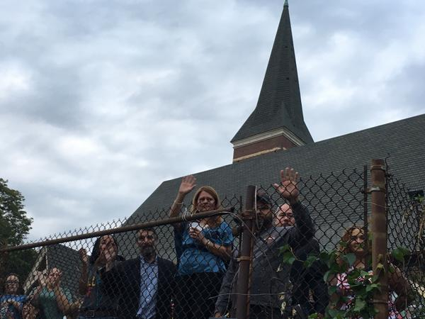 Nury Chavarria waves to her supporters from behind a fence on the grounds of the Iglesia de Dios Pentecostal Church in New Haven on Sunday. It was the first time Chavarria addressed the public since claiming sanctuary in the church last week.
