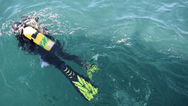 A diver swims to the buoy marking the wreck