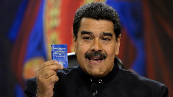 Venezuelan President Nicolas Maduro, holding up a small copy of the country's constitution, during a press conference on June 22, 2017.