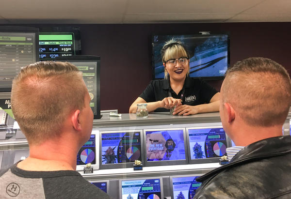 Yessenia Hinojos, a budtender at a Denver cannabis dispensary called The Green Solution, describes marijuana strains to A.J. Tarantino (left) and Philip Gurley. Both men are officers with Colorado State Patrol.