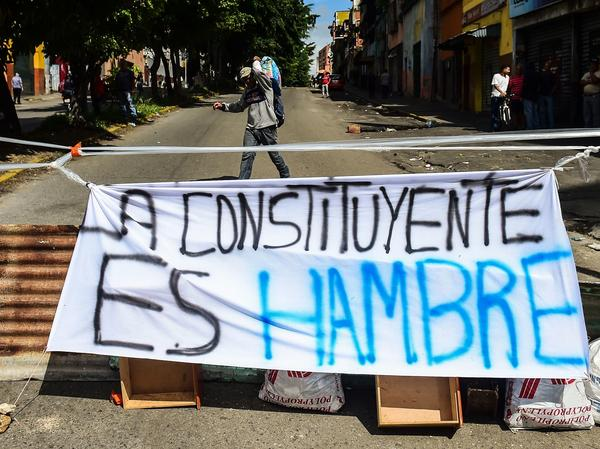 "Venezuelans began blocking  deserted streets Wednesday as the opposition held a two-day strike opposing President Nicolas Maduro's planned vote for a new Constituent Assembly. A banner reading ""The Constituent Is Hunger,"" is seen in Caracas' Petare neighborhood on Wednesday."