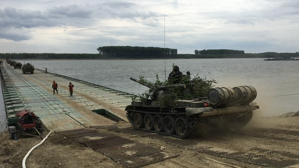 A Romanian army fighting vehicle prepares to cross a pontoon bridge across the Danube River.