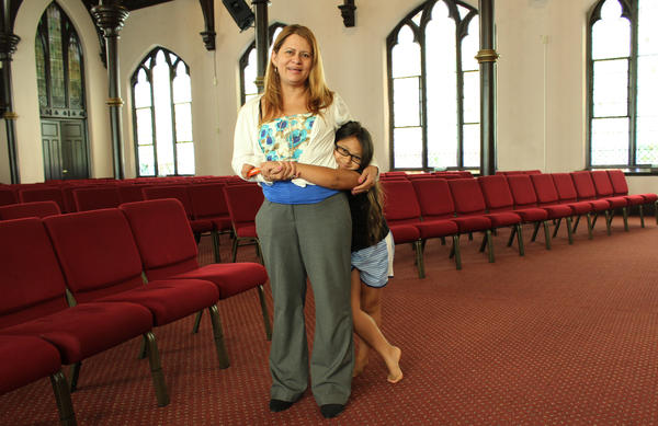 Nury Chavarria, 43, poses with her 9-year-old daughter, Hayley inside Iglesia De Dios Pentecostal Church in New Haven on Monday. Chavarria, who has lived in the U.S. for 24 years, sought sanctuary in the church last week when she was to have been deported