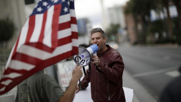 A protester shouts outside a Las Vegas courthouse as a February trial began for six defendants accused of taking arms against federal agents on Cliven Bundy's ranch. That case was declared a mistrial, but four of those defendants are now being retried.