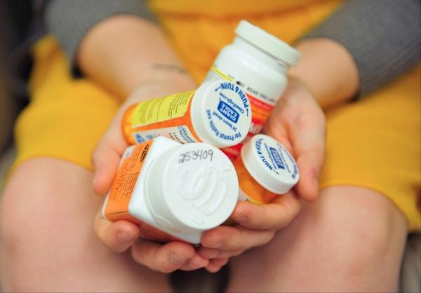 <p>Heidi Wyandt, 27, holds a handful of her medication bottles at the Altoona Center for Clinical Research in Altoona, Pa., on Wednesday, March 29, 2017, where she is helping test an experimental non-opioid pain medication for chronic back pain related to a work related injury she received in 2014.</p>