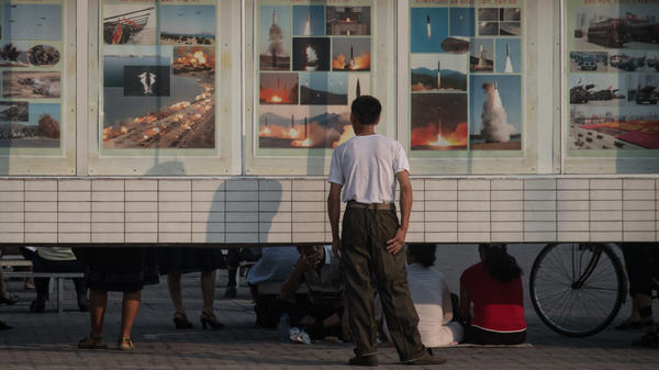 A man looks at images depicting missile launches and military exercises, on a display board in Pyongyang, North Korea, earlier this week.