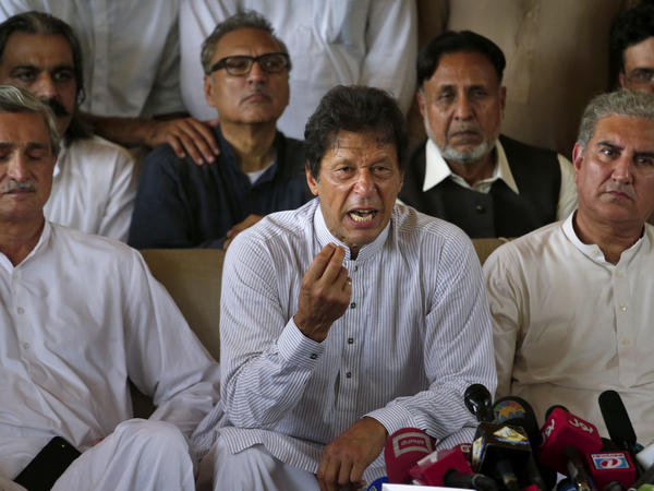 Pakistani opposition leader Imran Khan, center, addresses a news conference regarding the dismissal of Pakistani Prime Minister Nawaz Sharif in Islamabad on Friday. Opposition lawmakers, who petitioned the court for disqualification of Sharif, welcomed the court decision, saying it was a victory for justice.