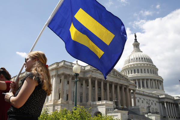 "A supporter of LGBT rights holds up an ""equality flag"" on Capitol Hill in Washington, Wednesday, July 26, 2017. (Jacquelyn Martin/AP)"