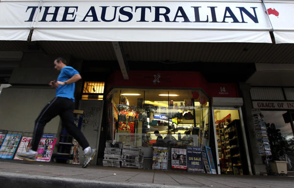 A jogger runs past a banner for <em>The Australian</em>, part of Rupert Murdoch's newspaper empire, in Sydney last year.