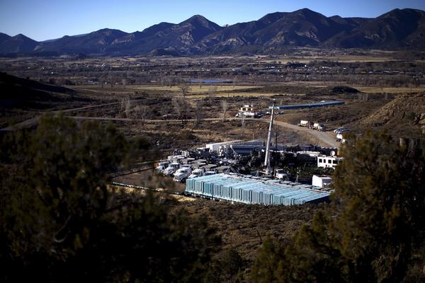 Trucks, water tanks and fracking equipment amassed on a gas pad near the town of Silt and the Grand Hogback Mountain Range.