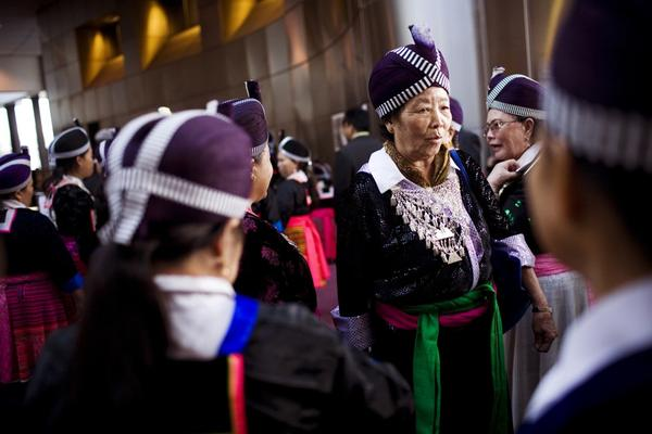 Hmong women wear traditional clothes, a sign of respect, during Vang's funeral.