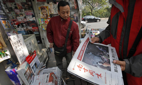 A man buys the latest edition of <em>Southern Weekly </em>at a newsstand near the newspaper's headquarters in Guangzhou, Guangdong province, China, on Thursday. The staff at the influential weekly rebelled to protest censorship by government officials; the newspaper was published Thursday after a compromise that called for relaxing some intrusive controls.