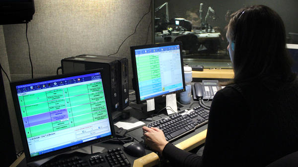 NPR Editorial Assistant Laura Lee takes and screens calls during a live broadcast of <em>Talk of the Nation</em>. Look just above Lee's head to see Neal Conan in the hosting chair on the other side of the glass.