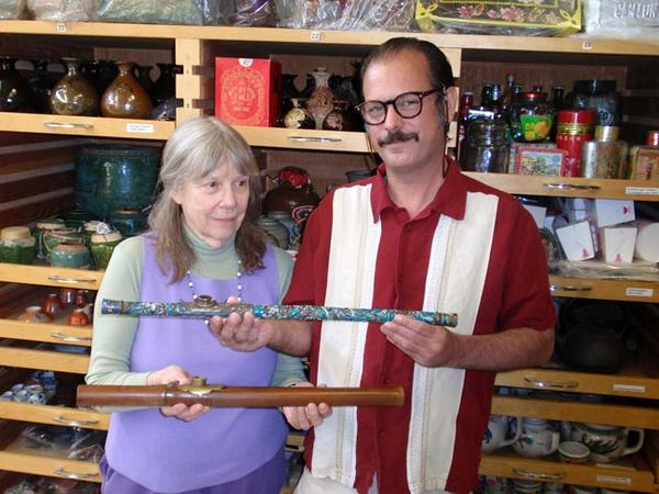 Donor Steven Martin and UI curator Priscilla Wegars hold antique opium pipes. Photo by Tom Banse