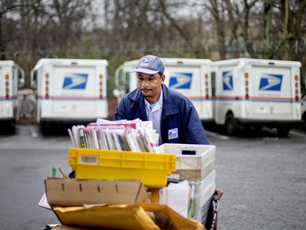 Veteran USPS letter carrier Michael McDonald gathers mail to load into his truck before making his delivery run in the East Atlanta neighborhood on Thursday, Feb. 7, 2013, in Atlanta.