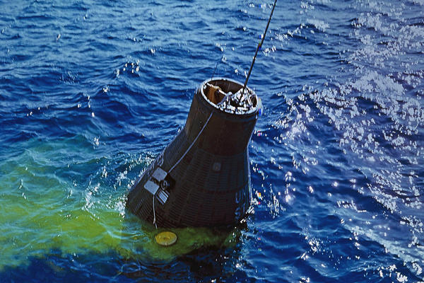 The Friendship 7 capsule containing Glenn is recovered from the Atlantic by the destroyer USS Noa. The yellow coloring in the water is dye to make the capsule more visible to the recovery crew.