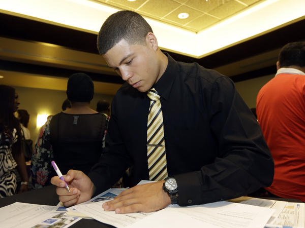 Gustavo Monteagudo fills out a job application at a July job fair in Miami Lakes, Fla. The U.S. unemployment rate in August dipped to a seven-year low of 5.1 percent.