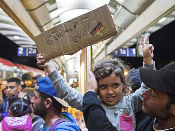 A migrant girl holds a sign expressing her love to Germany as she arrives at the train station in Saalfeld, central Germany, on Saturday. Hundreds of refugees arrived in a train from Munich to be transported by bus to an accomodation center.