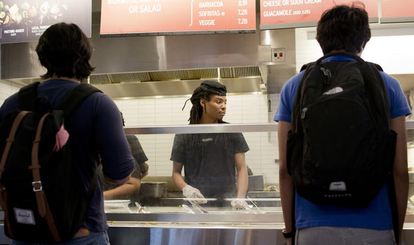 An employee serves customers in a Chipotle restaurant in Washington, DC on September 9, 2015. Chipotle, the burrito chain whose rocketing growth has fast-food giants like McDonald's reeling, is not slowing down: it plans to hire 4,000 new staff in one go.