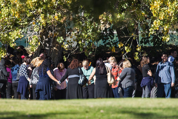 Evacuated workers pray in a circle on the San Bernardino Golf Course across the street from the scene of the shooting.