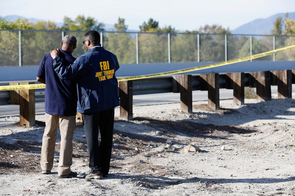 Members of the FBI Joint Terrorism Task Force stand near the site of a news conference following the shooting.