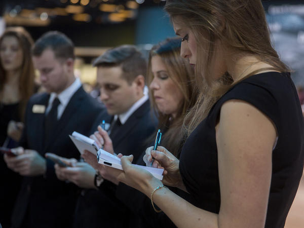 Product specialists take notes while training in the Daimler AG Mercedes Benz booth during the 2016 North American International Auto Show in Detroit on Tuesday.