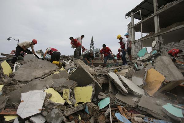 Volunteers search for survivors in the debris of buildings destroyed by an earthquake in Pedernales, Ecuador, on Sunday.