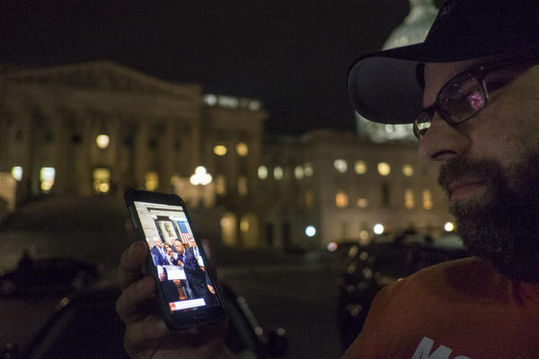 Outside the U.S. Capitol on Thursday, a supporter watches the proceedings being live-streamed from the House floor by Democrats taking part in a sit-in.