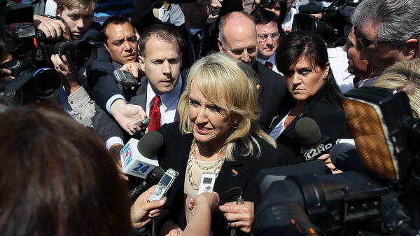 Arizona Gov. Jan Brewer speaks to the media after arguments at the U.S. Supreme Court to decide Arizona's controversial immigration legislation in 2012.