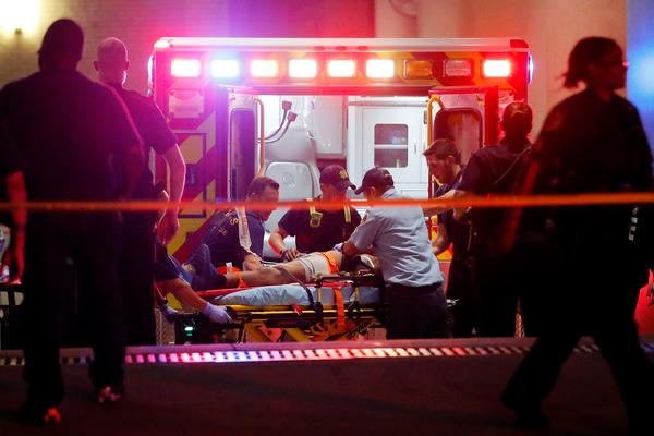 Emergency responders administer CPR to an unknown patient on a stretcher at Baylor University Medical Center as law enforcement officials stand nearby early Friday in Dallas.