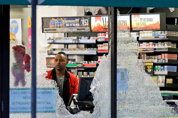 A clerk looks through broken windows, which were shot out at a convenience store in downtown Dallas.