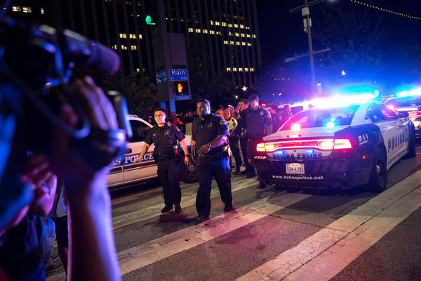 Bystanders stand near police barricades following the sniper shooting in Dallas on Thursday.