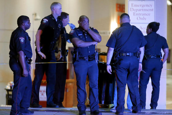 A Dallas police officer covers his face as he stands with others outside the emergency room at Baylor University Medical Center in Dallas. Snipers opened fire on police officers Thursday night, killing some of the officers.