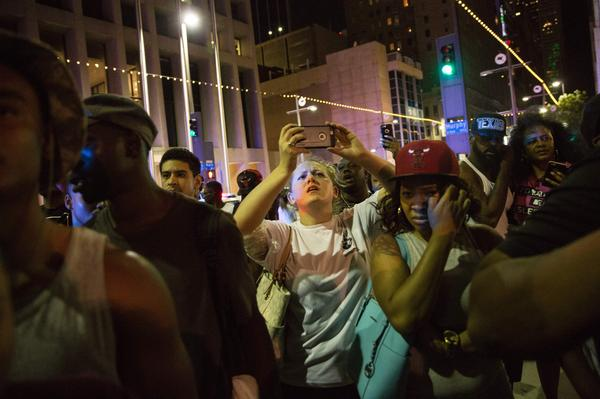 Protestors react as police officers arrest a bystander in downtown Dallas following Thursday's shooting.