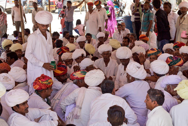 Lumbaram, standing on the left, attends to <em>panches,</em> or village elders, at a memorial service for his father. He will need the elders' permission to break Durga's marriage.
