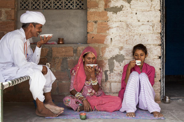 Durga and her parents relax in the courtyard of their two-room concrete block home.