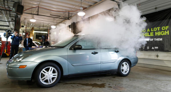 Simulated marijuana smoke billows out of the windows of a car during a demonstration by the Colorado Department of Transportation.