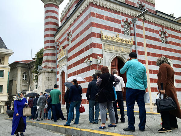"Turks line up outside the Istanbul governor's office, one of the ""crisis management centers"" set up for those who believe they were wrongly suspended, fired or arrested following the July 15 coup attempt."
