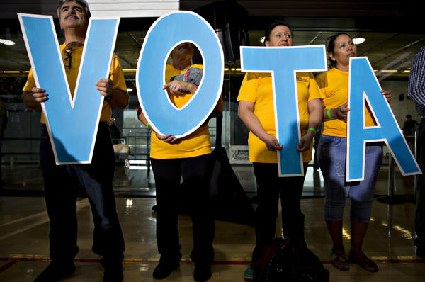 """Attendees hold letters reading """"vote"""" in Spanish during a campaign event with Tim Kaine."""