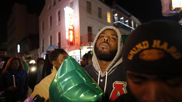 People gather Sunday night for a vigil at Bourbon Street and Iberville Street for Demontris Toliver, 25, who was killed early Sunday morning in a shooting in the French Quarter of New Orleans.